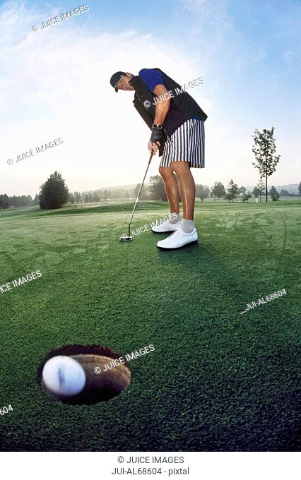 Low angle view of a man putting his ball into the hole on a golf course