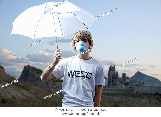 Man with umbrella and contamination mask near a cement works