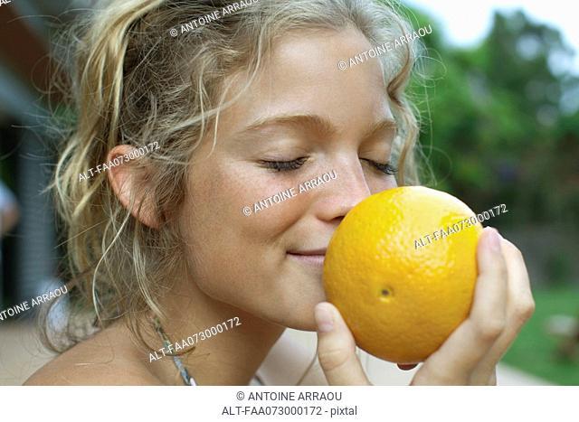 Woman smelling fresh orange
