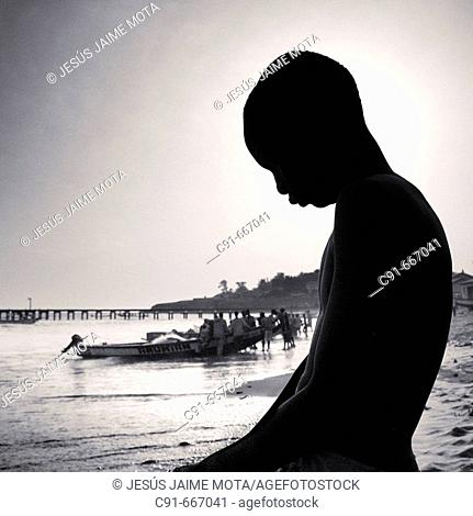 Silhouette of young fishermen and boat. Gambia