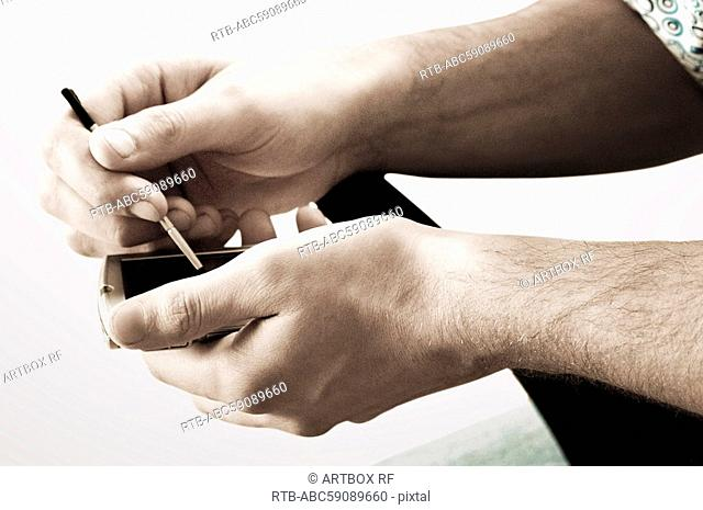 Man's hand operating a personal data assistant