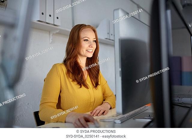 happy woman with computer working at office