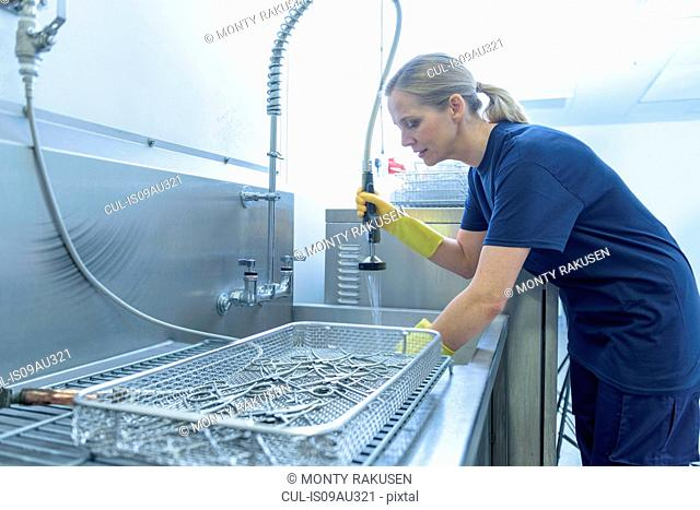Worker cleaning surgical instruments in ultrasonic bath in surgical instrument factory