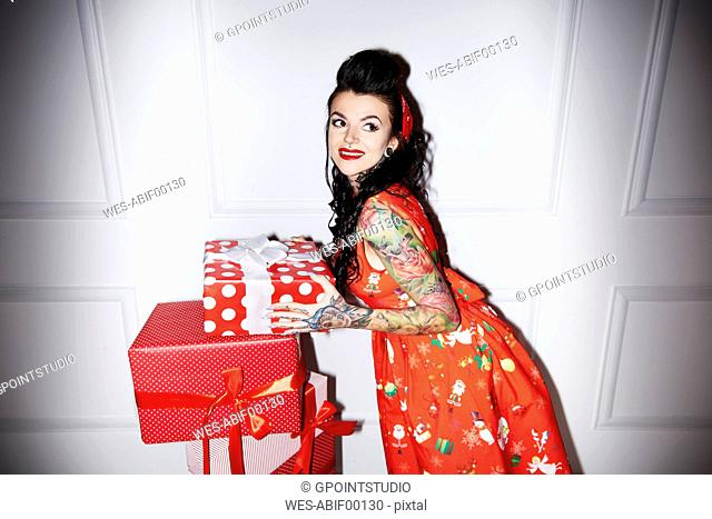 Portrait of tattooed woman with stack of gifts