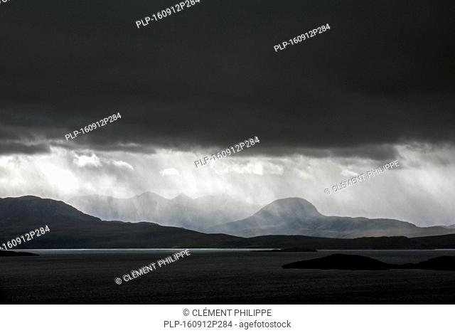 Black stormy sky and downpour during rain storm over desolate wilderness of Coigach, Wester Ross in the Northwest Highlands of Scotland