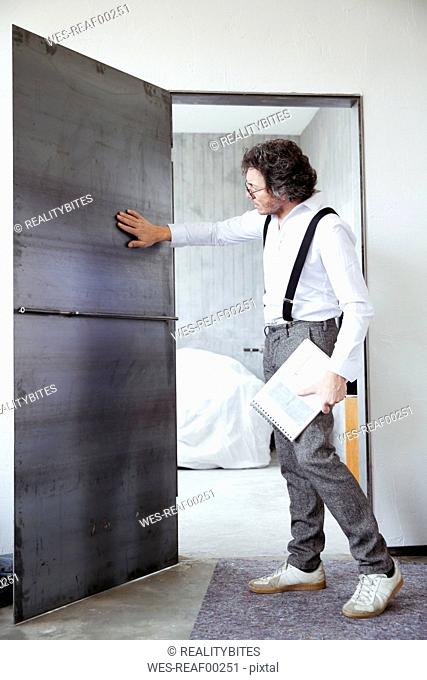 Architect checking steel door at construction site