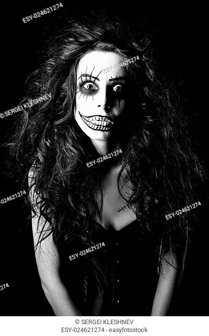 Beautiful young woman in the image of a sad gothic freak clown. Black and white