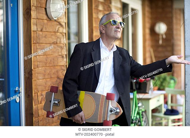 Senior businessman wearing suit and holding longboarding, Freiburg im Breisgau, Baden-Württemberg, Germany