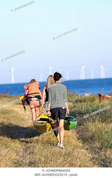 Mother with daughter carrying kayaks