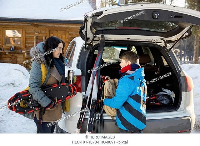 Mother and son unloading winter sports gear from car