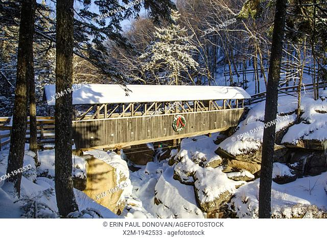Franconia Notch State Park - Sentinel Pine Covered Bridge during the winter months. It is a footbridge which crosses over the Pemigewasset River in Lincoln