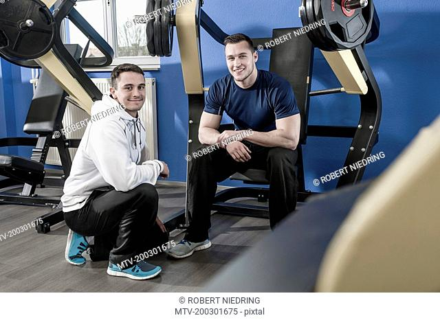 Two smiling young men in gym