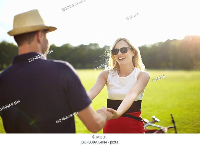 Couple holding hands and swirling each other around in park