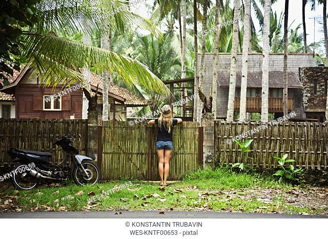 Indonesia, Java, back view of woman leaning on garden gate looking at houses