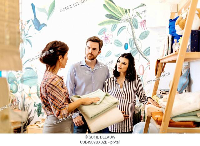 Shop keeper showing items to pregnant couple