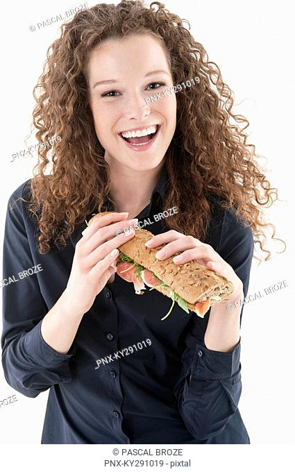 Woman holding a sandwich and laughing
