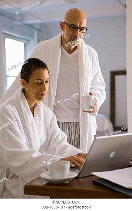 Side profile of a mature woman using a laptop with a mature man standing beside her