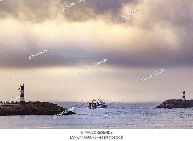Fishing boat entering the harbor after a day fishing into the sea