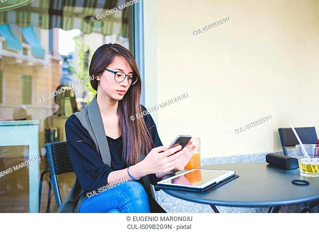 Young woman reading smartphone texts at sidewalk cafe