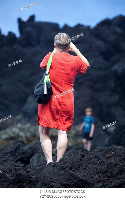 Woman taking a picture in the coast. Sao Miguel Island, Azores, Portugal