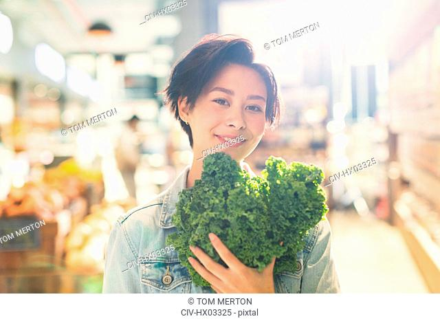 Portrait smiling young woman holding fresh kale in grocery store market