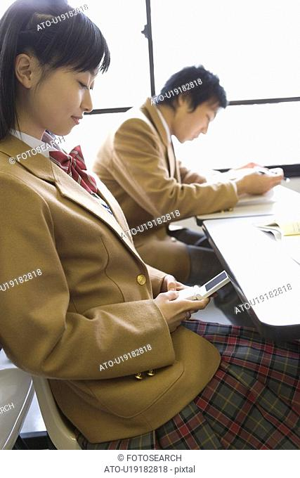 High School Girl Using Mobile Phone Secretly During Lecture, Selective Focus