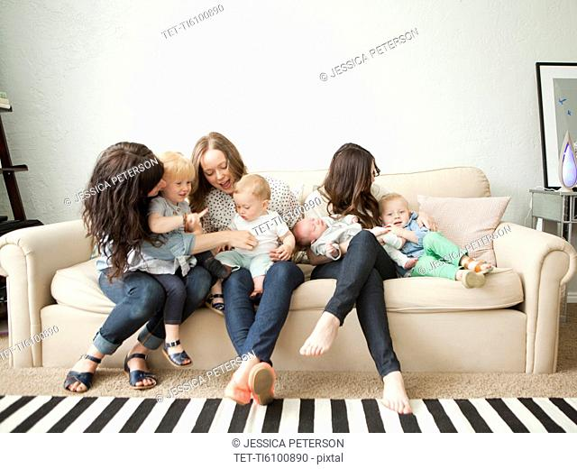 Three young mothers with toddler girl 2-3 and two baby boys 2-5 months, 6-11 months sitting together on sofa