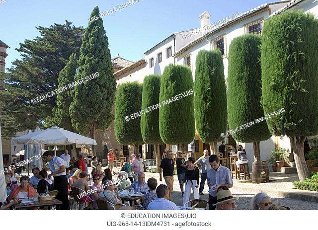 Groups of people sitting at tables and chairs of outdoor street cafe in the old city of Ronda, Spain