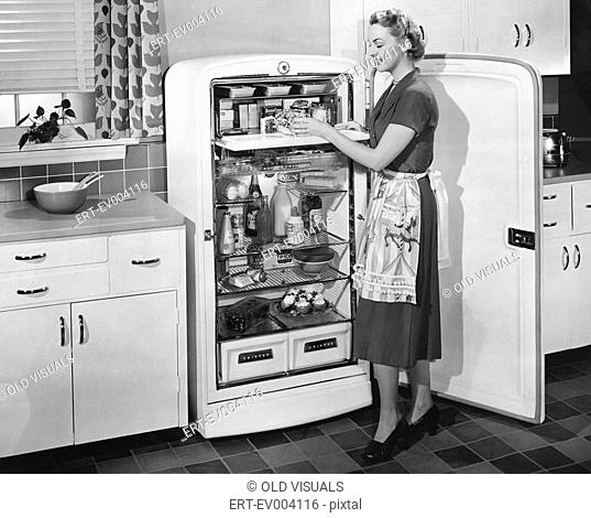 Woman with open refrigerator All persons depicted are not longer living and no estate exists Supplier warranties that there will be no model release issues