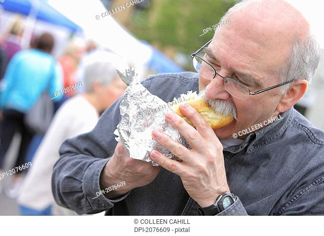 Senior man biting into a hot dog, troutdale oregon united states of america