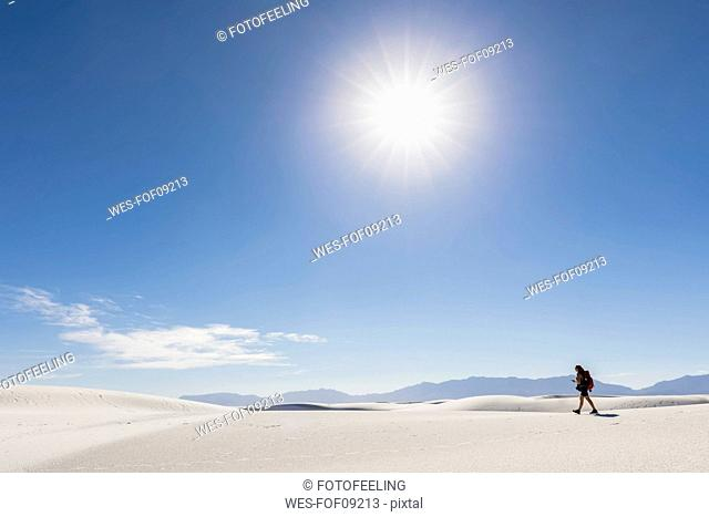 USA, New Mexico, Chihuahua Desert, White Sands National Monument, woman hiking on dune