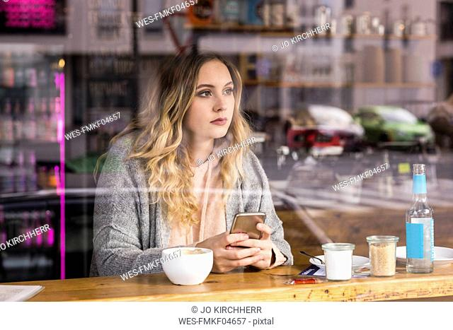 Portrait of pensive young woman in a coffee shop looking through window