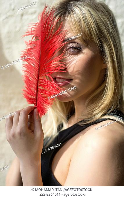 Alluring young blond woman hiding face with a red feather smiling