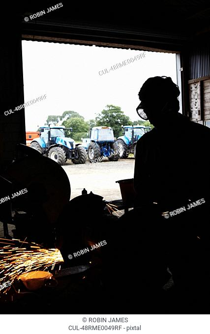 Silhouette of metal worker in shop