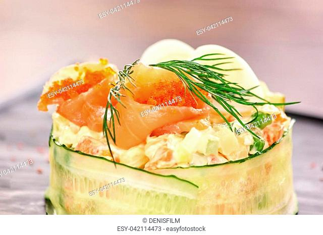Olivier salad with salmon and tobiko caviar. Tasty olivier salad served with salmon, tobiko caviar, dill and eggs. Appetizing salad in restaurant