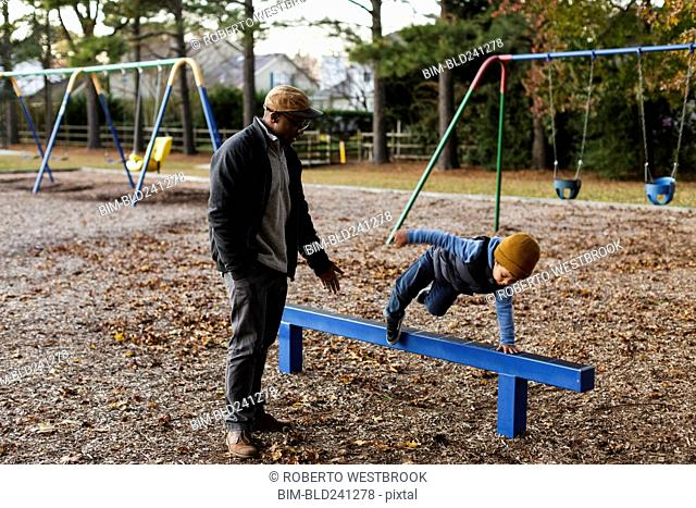 Father watching son jumping over playground beam