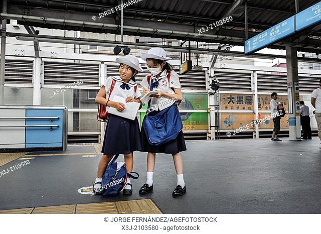 Schoolgirls waiting for the train at a railway station, Tokyo, Japan, Asia