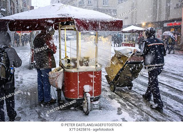 A hot chestnut stall during winter snow storm on Istiklal Caddesi, Beyoglu, Istanbul, Turkey,