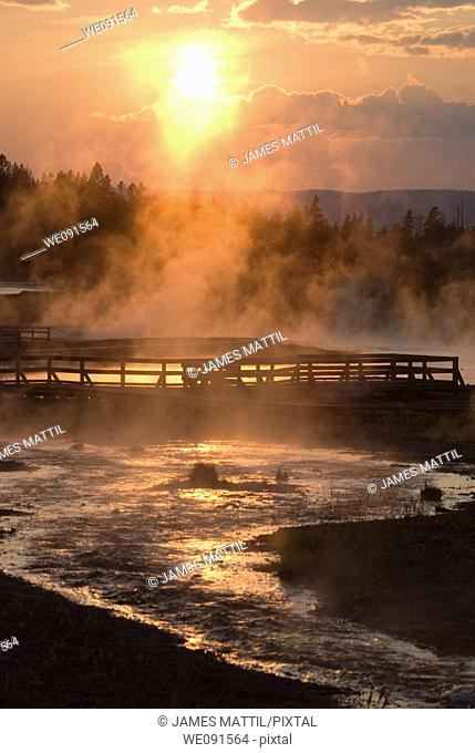 The setting sun reflecting on Firehole Lake geothermal area and boardwalk suggests a boiling pool of magma below