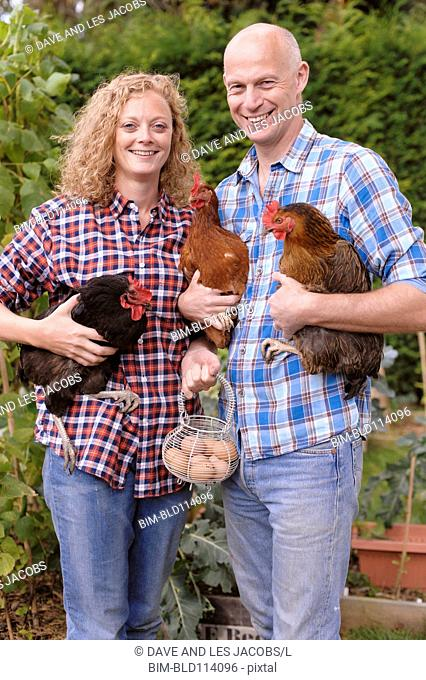 Caucasian farmers smiling with chickens