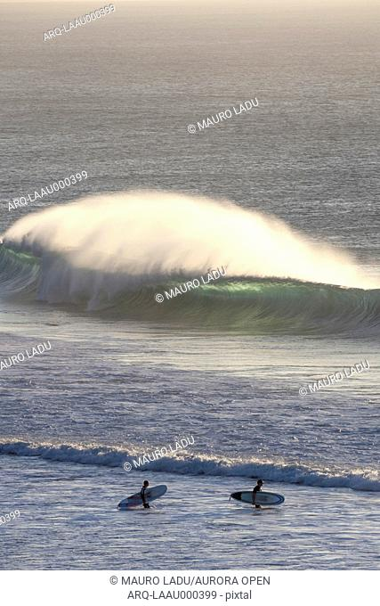 Two surfers on the beach with big waves breaking in the background