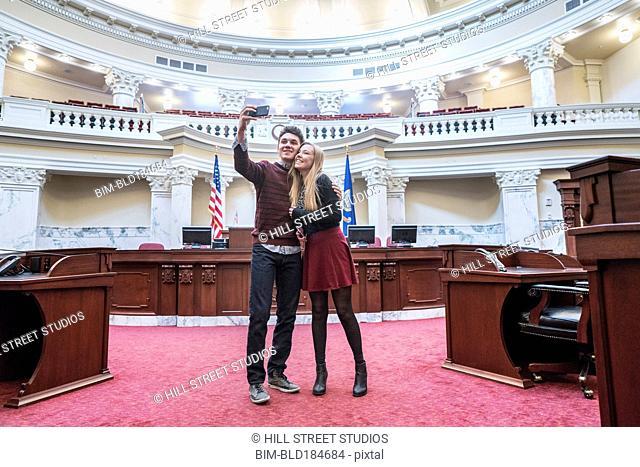 Caucasian couple taking selfie in capitol building