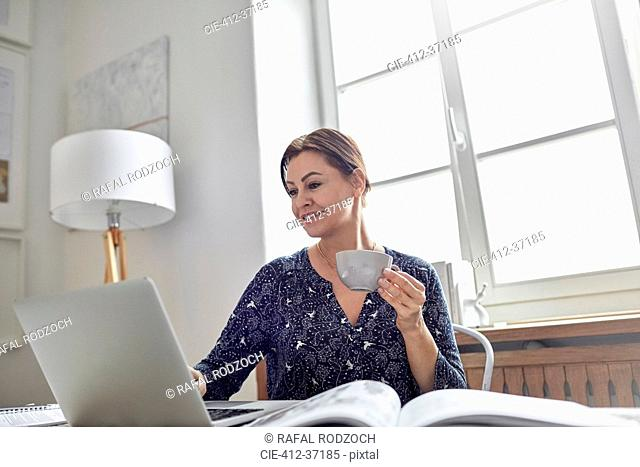 Smiling businesswoman drinking coffee and working at laptop