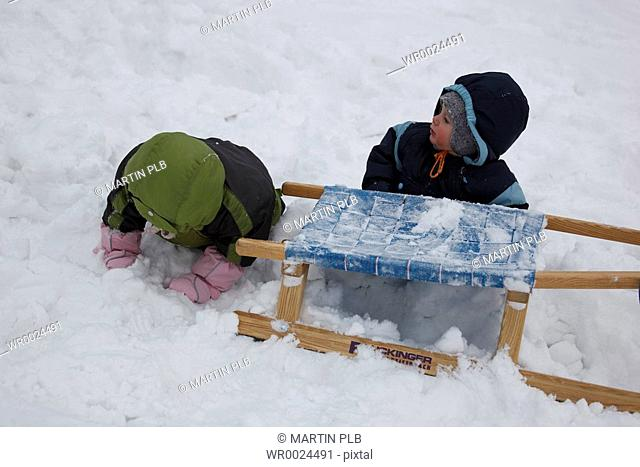 little children playing with toboggan