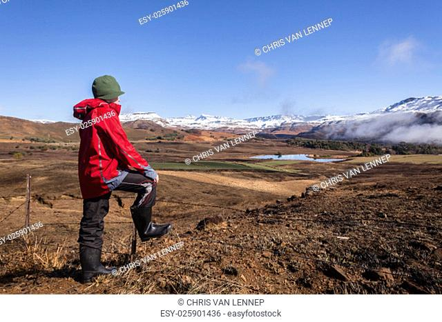 Teen boy overlooks mountain snow valley green black contrasted scenic landscape