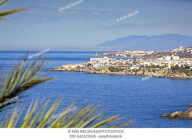 Nerja, Costa del Sol, Malaga Province, Andalusia, southern Spain. View from near Maro to Nerja with the lighthouse of Torrox Costa visible behind