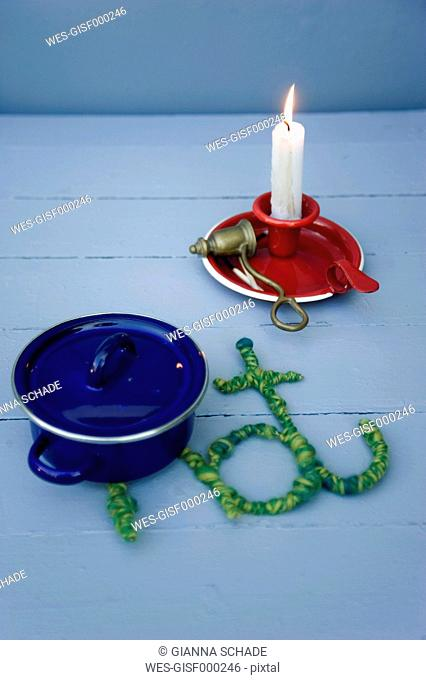 Blue cooking pot on table mat made from wool and wire with burning candle in background