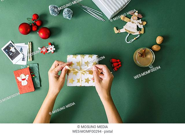 Woman's hands packing Christmas gift