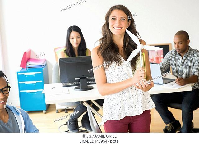 Businesswoman holding wind turbine model in office