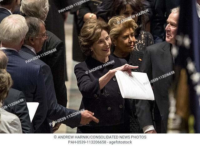 Former Defense Secretary Leon Panetta, left, greets former President George Bush, right, as he and his wife, former first lady Laura Bush follow the flag-draped...